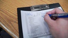 Chiuda sull'uomo la scrittura della mano che fa la nota clip L'uomo fa le note nel documento immagini stock libere da diritti