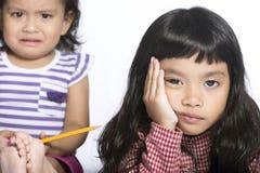 Chiuda sulla bambina due nella discussione su fondo bianco Immagini Stock