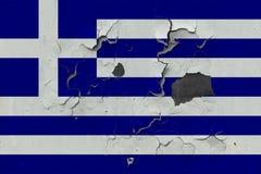 Chiuda sulla bandiera grungy, nociva e stagionata della Grecia sulla parete che pela la pittura per vedere interno superficie fotografia stock