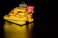 Chiuda sulla barra di oro pura nei precedenti neri Fotografia Stock