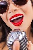 Chiuda sulla bocca di canto della donna & sul microfono dell'annata Fotografie Stock