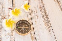Chiuda sulla bussola e la plumeria tropicale fiorisce sulla tavola di legno Fotografie Stock