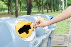 Chiuda sulla carta velina di lancio della mano nel recipiente di riciclaggio, concetto di ambientale Fotografie Stock