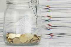 Chiuda sulla casa della sfuocatura con le monete di oro in bottiglia Fotografia Stock Libera da Diritti