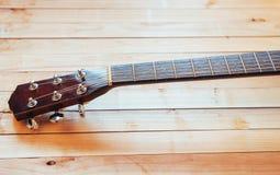 chiuda sulla chitarra classica acustica del collo su un fondo di legno leggero Fotografia Stock