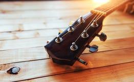 chiuda sulla chitarra classica acustica del collo su un fondo di legno leggero Fotografia Stock Libera da Diritti