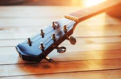 chiuda sulla chitarra classica acustica del collo su un fondo di legno leggero Immagini Stock Libere da Diritti