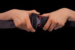 Chiuda sulla cintura di sicurezza di uso di due mani Immagine Stock