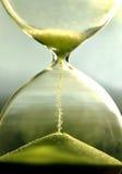 Chiuda sulla clessidra che conta il tempo di attesa con la vista della sabbia Immagine Stock