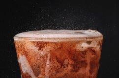 chiuda sulla cola del ghiaccio nella soda della bolla e di vetro che spruzza sulle sedere nere Fotografia Stock