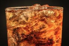 chiuda sulla cola del ghiaccio nella soda della bolla e di vetro sul nero Immagini Stock