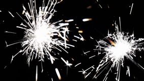 Chiuda sulla combustione delle stelle filante di natale Fuochi d'artificio accesi su fondo nero stock footage
