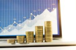 Chiuda sulla crescita impilata moneta sul grafico finanziario del grafico in computer portatile Fotografia Stock Libera da Diritti