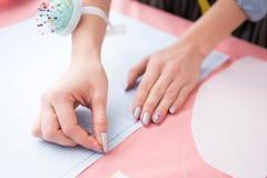 Chiuda sulla donna alla fabbrica dell'indumento che prende le misure su tessuto per ritaglio immagini stock libere da diritti