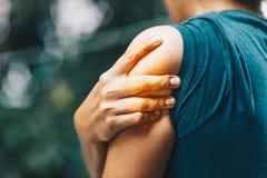 Chiuda sulla donna che ha dolore in spalla immagini stock libere da diritti