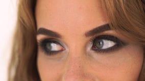 Chiuda sulla donna con gli occhi fumosi compongono Affronti la donna del fascino con trucco luminoso e perfetto Bella donna del r stock footage