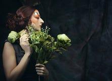Chiuda sulla donna del redhair del ritratto con creativo luminoso compongono la tenuta dei fiori asciutti Immagini Stock
