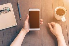 Chiuda sulla donna dell'Asia della mano che utilizza il telefono nella caffetteria con l'annata Fotografia Stock Libera da Diritti