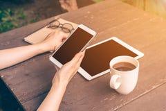 Chiuda sulla donna dell'Asia della mano che utilizza il telefono nella caffetteria con l'annata Fotografie Stock Libere da Diritti