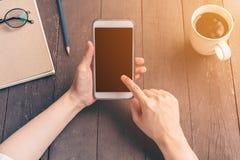 Chiuda sulla donna dell'Asia della mano che utilizza il telefono nella caffetteria con l'annata Fotografia Stock