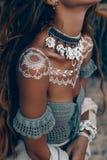Chiuda sulla donna di boho con l'ornamento tradizionale all'aperto al tramonto Immagini Stock