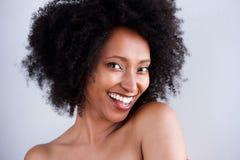 Chiuda sulla donna di colore con le spalle nude che sorride sul fondo grigio fotografia stock
