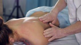 Chiuda sulla f il terapista di massaggio che massaggia la parte posteriore del ` s della donna archivi video