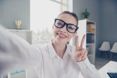 Chiuda sulla foto bella lei il suo v-segno che del telefono dei braccia di mani degli occhiali di occhiali di signora di affari a immagine stock