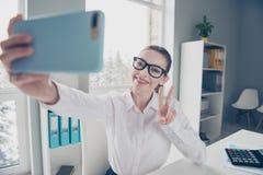 Chiuda sulla foto bella lei il suo v-segno che del telefono dei braccia di mani degli occhiali di occhiali di signora di affari a fotografia stock