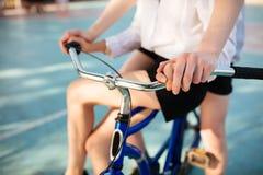 Chiuda sulla foto dei corpi della donna e del giovane che guidano insieme sulla bicicletta blu Mani della donna e dell'uomo che t fotografie stock