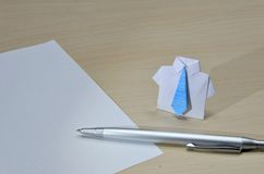 Chiuda sulla foto del vestito di origami con il legame blu vicino a carta e della penna sullo scrittorio Fotografia Stock