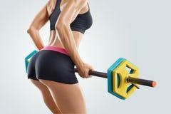 Chiuda sulla foto dell'allenamento della donna di forma fisica con il bilanciere alla palestra Fotografia Stock
