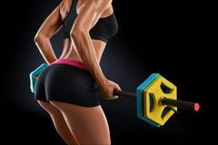 Chiuda sulla foto dell'allenamento della donna di forma fisica con il bilanciere alla palestra Immagini Stock