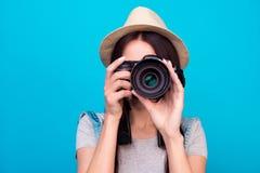 Chiuda sulla foto della donna in cappello su fondo blu che prende una foto immagini stock