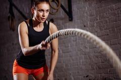 Chiuda sulla foto della donna che fa l'allenamento della corda di battaglia vicino al muro di mattoni bianco fotografia stock libera da diritti