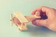 Chiuda sulla foto della mano dell'uomo che tiene l'aeroplano di legno del giocattolo sopra fondo di legno Immagine filtrata conce Immagini Stock