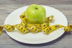 Chiuda sulla foto della misura di nastro arrotolata intorno ad una mela sulla p bianca immagine stock libera da diritti