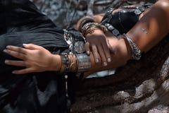 Chiuda sulla foto delle mani con gli accessori tribali etnici Fotografia Stock