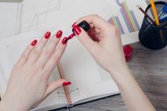 Chiuda sulla foto delle mani del ` s della donna che dipingono i chiodi sopra spirito del desktop immagini stock libere da diritti