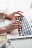 Chiuda sulla foto delle mani femminili che scrivono sulla tastiera del computer portatile con una tazza di cappuccino modellato Fotografia Stock Libera da Diritti