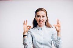 Chiuda sulla foto di giovane donna castana divertente che mostra il gesto GIUSTO, esaminante la macchina fotografica su fondo bia Fotografia Stock Libera da Diritti