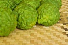 Chiuda sulla frutta verde del bergamotto messa sulla stuoia di bambù Immagini Stock Libere da Diritti