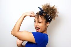 Chiuda sulla giovane donna afroamericana fresca che flette il muscolo del bicipite fotografie stock libere da diritti