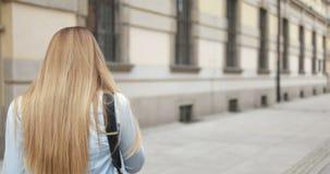 Chiuda sulla giovane donna attraente che per mezzo del suo telefono cellulare archivi video