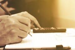 Chiuda sulla giovane donna con il calcolatore che conta facendo le note ad uff Fotografie Stock Libere da Diritti