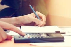 Chiuda sulla giovane donna con il calcolatore che conta facendo le note ad uff Fotografia Stock