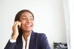 Chiuda sulla giovane donna di affari africana felice in ufficio che parla sul telefono cellulare immagini stock libere da diritti