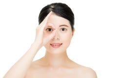 Chiuda sulla giovane donna sorridente con il gesto del dito sugli occhi Immagini Stock