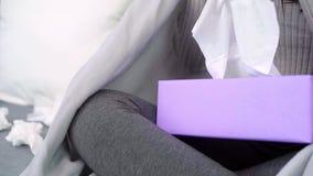Chiuda sulla giovane emicrania asiatica malata di tatto della donna che si siede su una sedia avvolta in coperta grigia nel suo s video d archivio