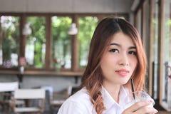 Chiuda sulla giovane tazza di caffè asiatica attraente della tenuta della donna e sull'esame alla macchina fotografica il caffè c Fotografia Stock